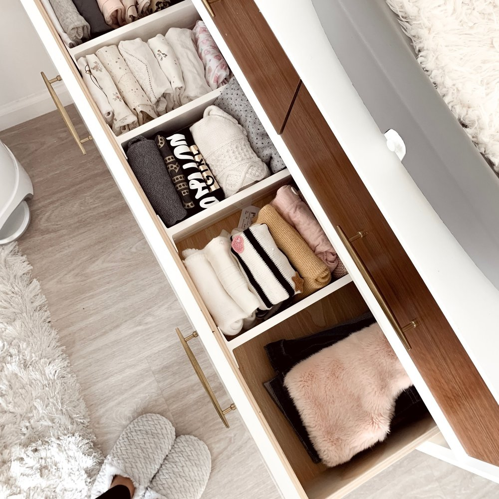 Drawers with folded clothes and white slippers