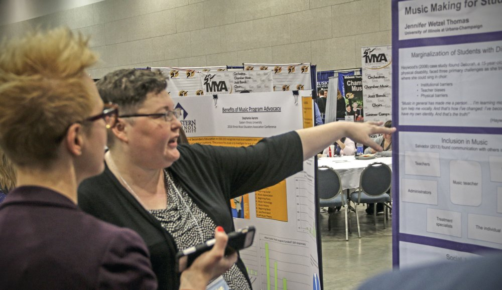 Two female professors discussing research at the i.m.e.c. poster session.