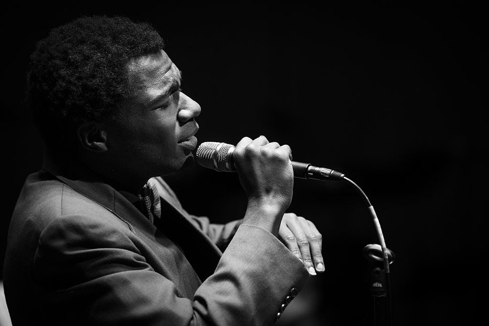 African American high school student singing with a microphone in an All-State vocal jazz performance.