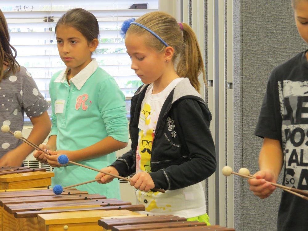 Students performing on wooden xylophones at an elementary festival.