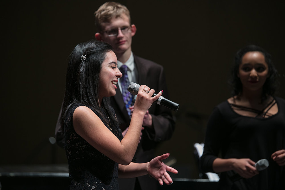 Female soloist singing into microphone during a vocal jazz performance