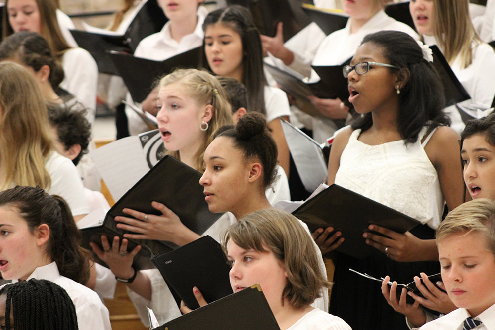 Female students singing with junior chorus at a district festival