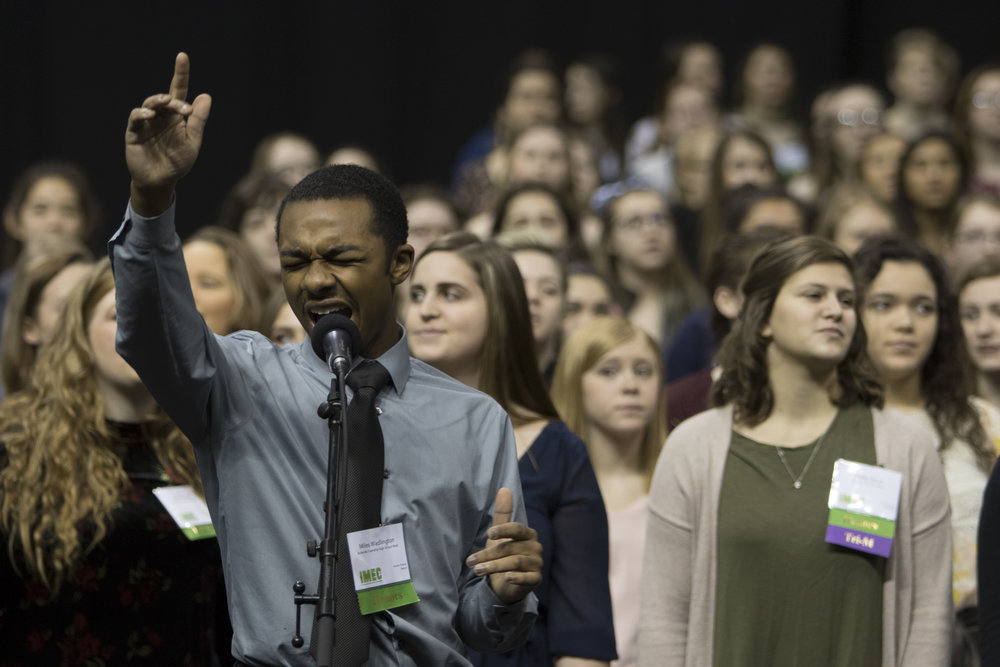 Student soloist singing with All-state chorus in rehearsal