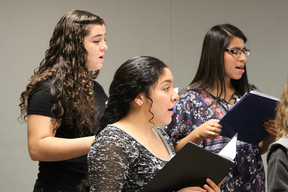 High school female students rehearsing for a vocal jazz performance