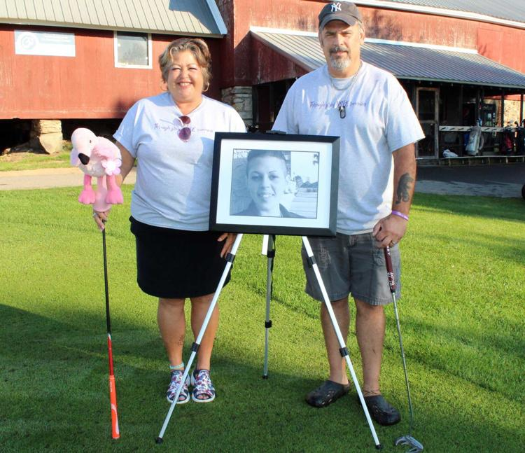 Memorial golf event: Kelly and Jody Wells pose with a photo of their daughter Celeste on Sunday at the second annual Celeste Wells Memorial Golf Tournament at Stone Creek Golf Club. The event raised money for HOPE For Bereaved in Fulton, and also for Road2RecoveryCNY.