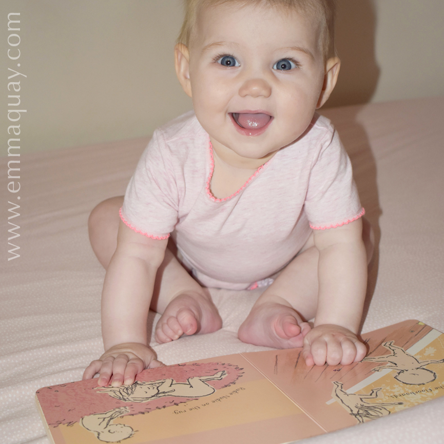 Little six-month-old Ivy sitting up for the first time, with her RUDIE NUDIE board book by Emma Quay (ABC Books) - www.emmaquay.com