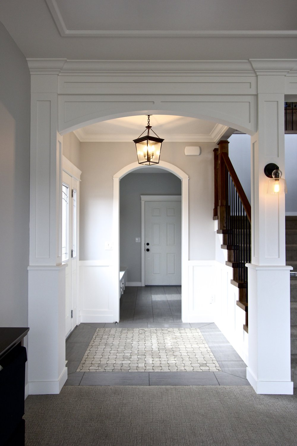 Metric Design Centre, Interior Design, Saskatoon, Residential Design, New Home Build, Transitional Design, Front Entrance, Mudroom, White Molding and Trim, Door, Marble Tile Inset, Pendant Lighting, White Trim and Molding, Carpet, Column, Staircase.jpg