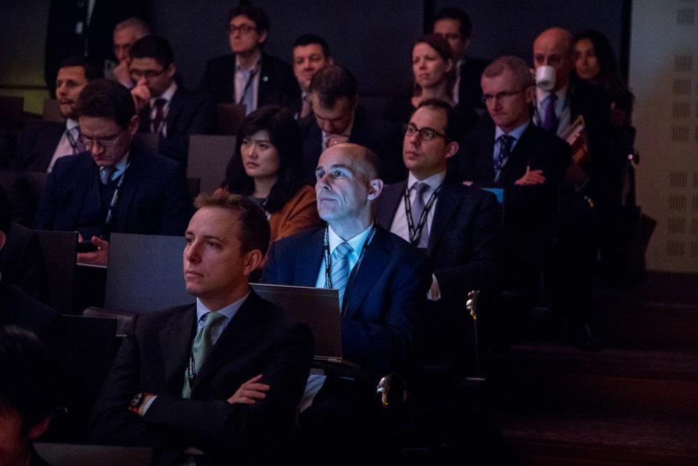 Man in suit on laptop in the auditorium