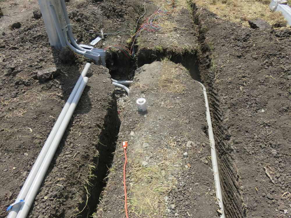 The ground is carefully trenched for the wiring conduit.