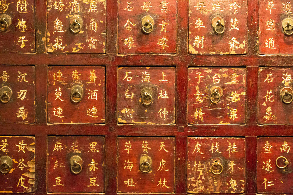 Chinese herbs are traditionally kept in cabinets of many drawers extending high up, sometimes covering an entire wall or more in a pharmaceutical workplace. The drawers are labeled and skilled practitioners, after working hundreds of times through the same formulas, will memorize patterns of the drawers, much like the ingredients of the formulas.  We have a big cabinet in our herbal pharmacy.