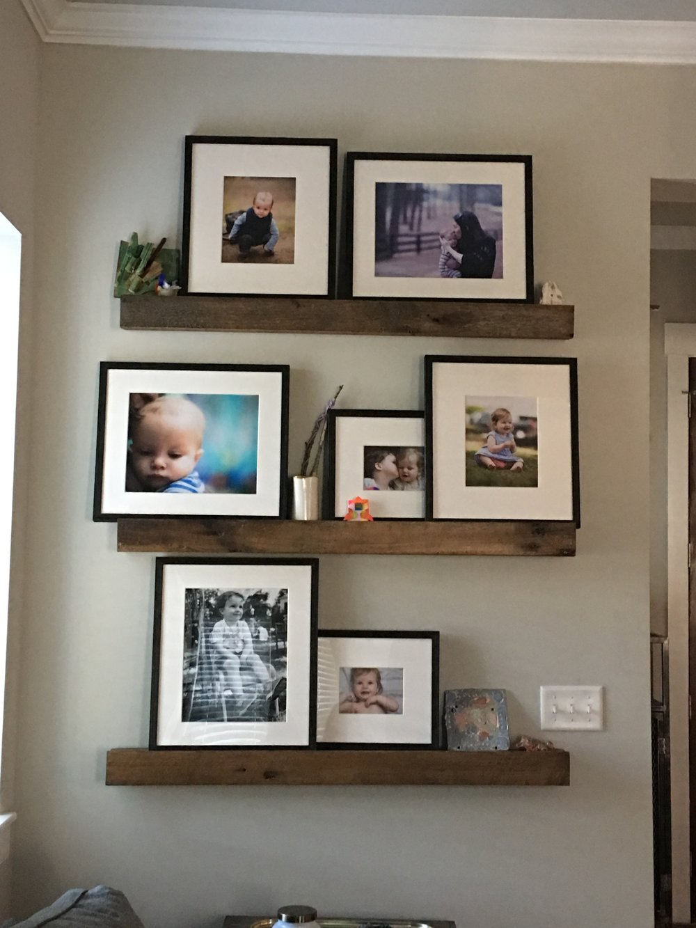 """This spot in our living space has my heart. I had my dad (he's awesome) make these amazing shelves out of barnwood he salvaged. He's been making stuff from reclaimed woods way before it was """"cool"""" ;)I love it!    On the shelves are photos Matt has taken and art our kids have made, from ceramic figures to sticks wrapped in yarn.    I love these shelves so much that I'm having another one made."""