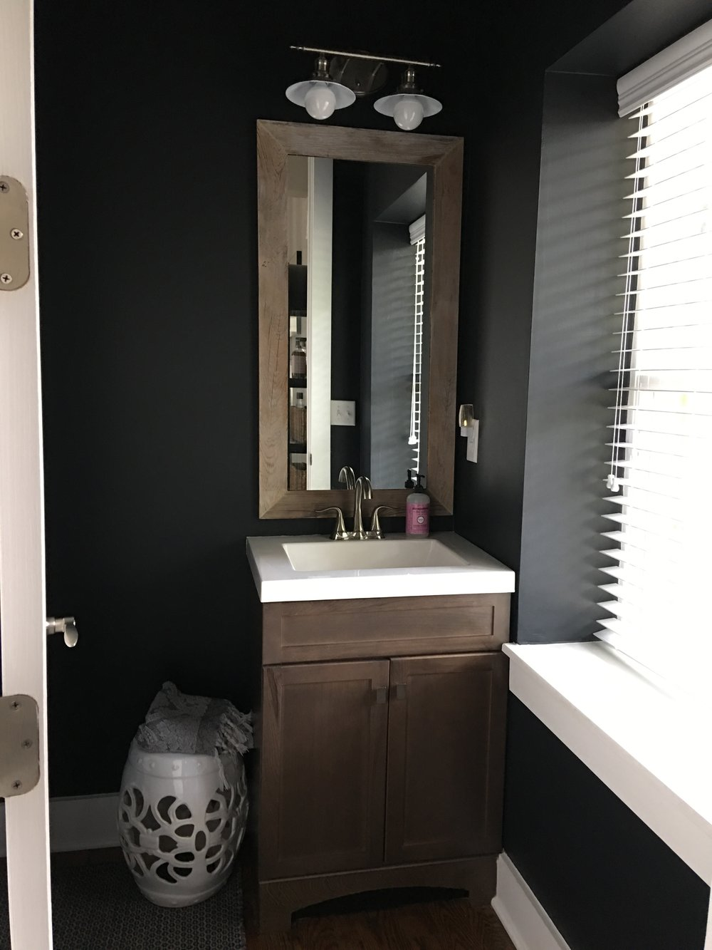 This is a photo of our little half bath. I had it painted a super deep navy — almost black. It's crisp and gets tons of light, like all of our home. It has a hand-stitched red barn piece Matt's mom did, and etchings along with vintage milk glass vases I fill with fresh flowers from our yard (or  Amelia's flower truck ) all the time. I love this little bathroom.
