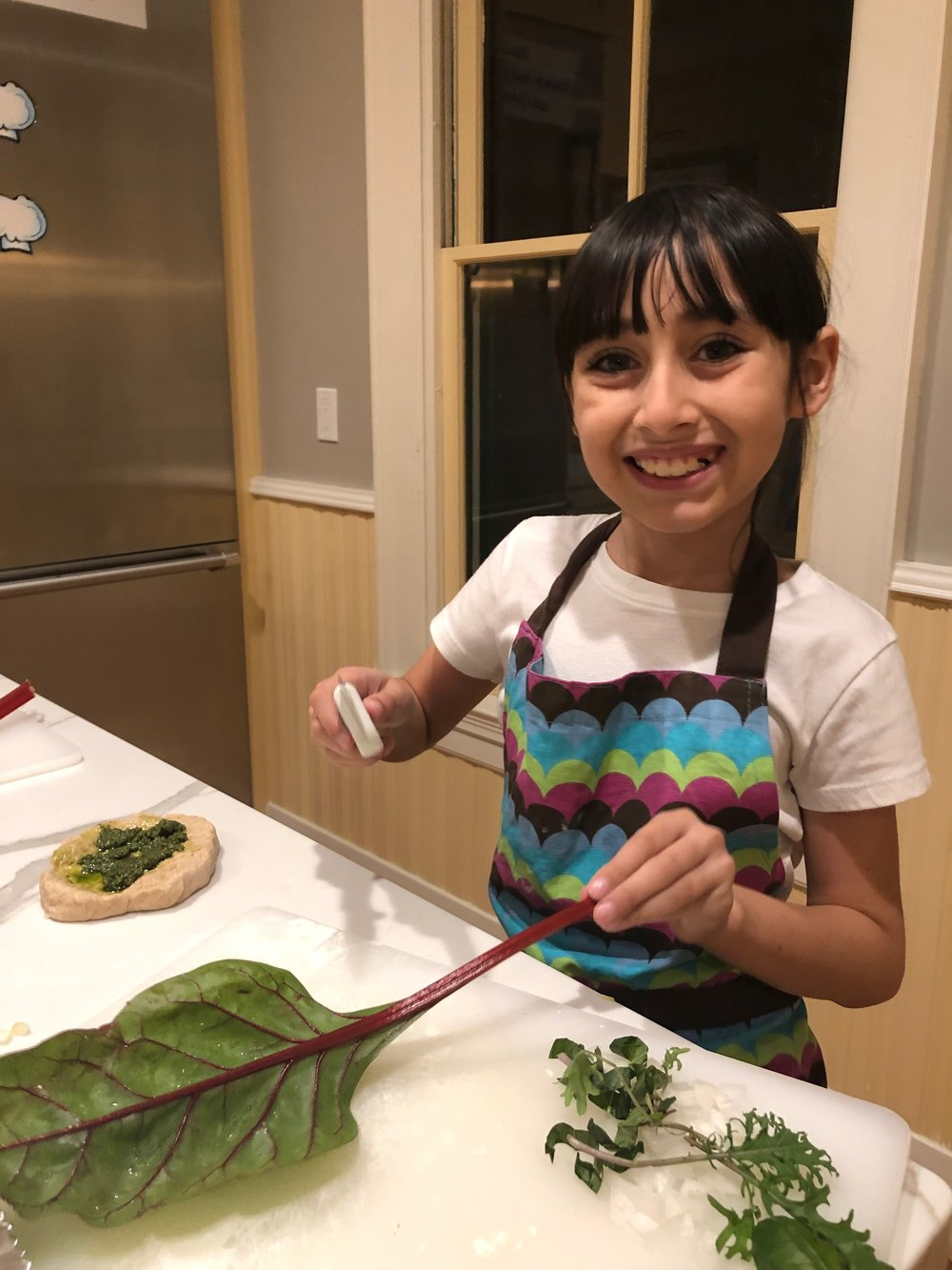 Mentee learning how to make pesto pizza at Olivewood Gardens.