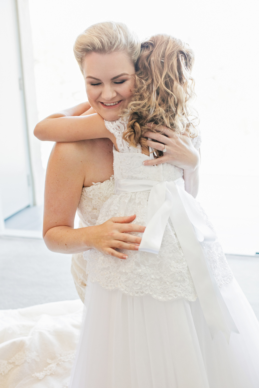 wedding-0317-flowergirl-moments-hugs-bride-queensland.jpg