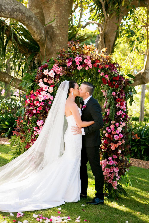 wedding-0050-ceremony-flowers-garden-arch-kiss-queensland.jpg