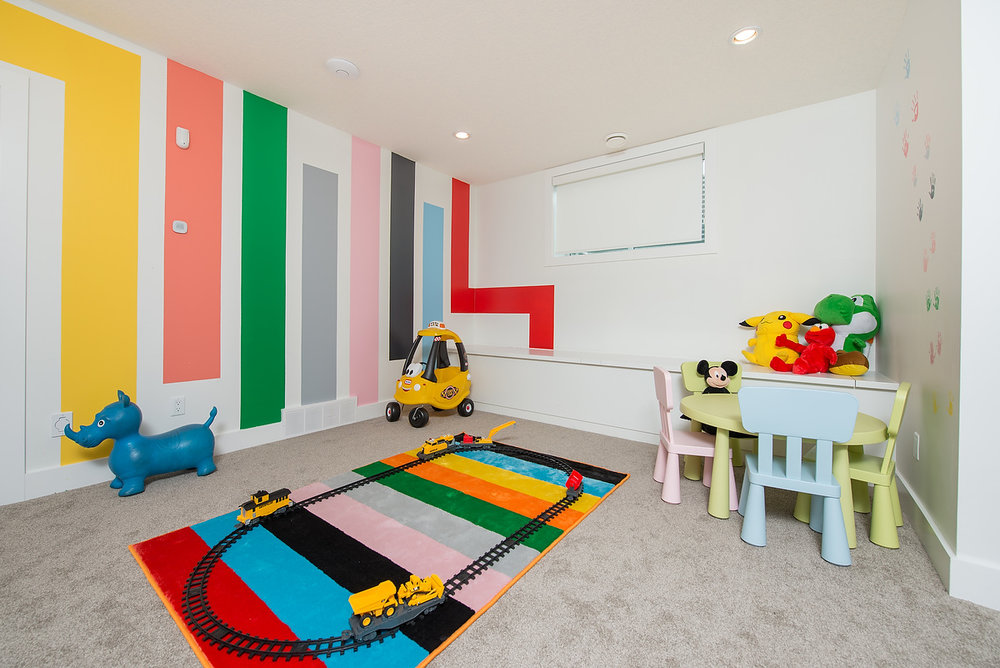 Playful wall treatments reflect the energy of the kids in the play room.