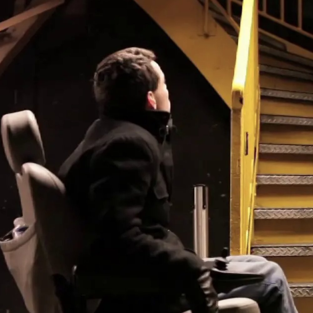 [Image Description: White man in a power chair looks up a flight of yellow stairs, the back of his head facing the camera.]