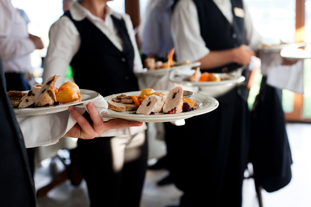K'Mich Weddings - wedding planning - catering wait staff in black and white holding plates with food - image