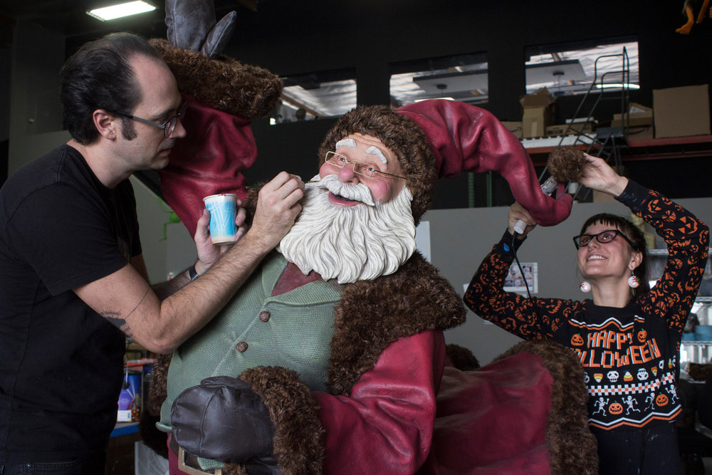 Romaire Studios artists putting finishing touches on outdoor Santa figure