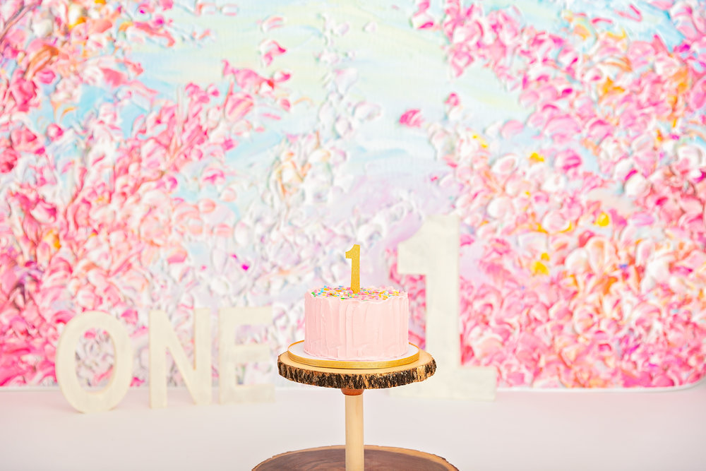 one year old pink smash cake on cake stand with birthday One background
