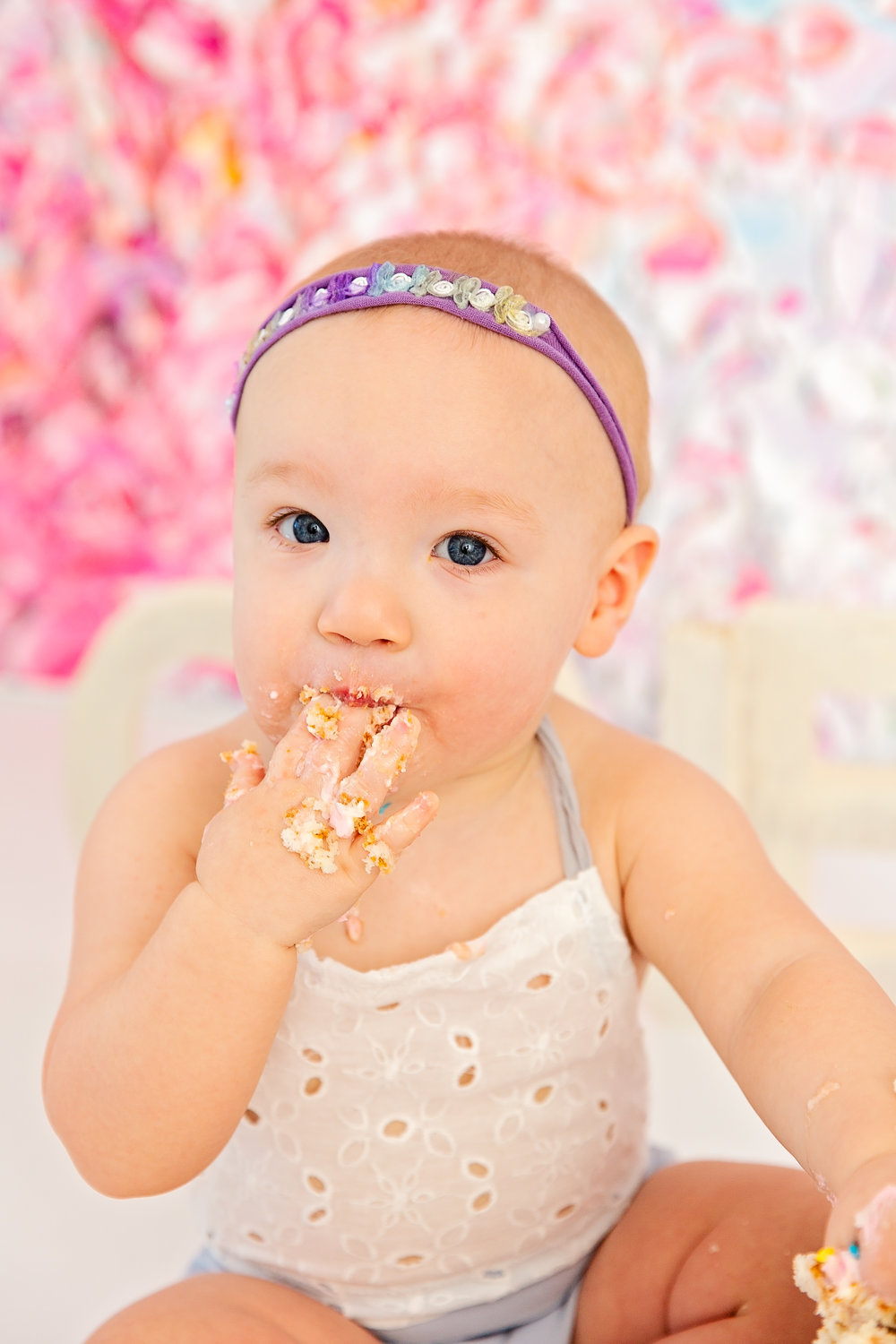 close up of one year old baby girl eating cake off hand