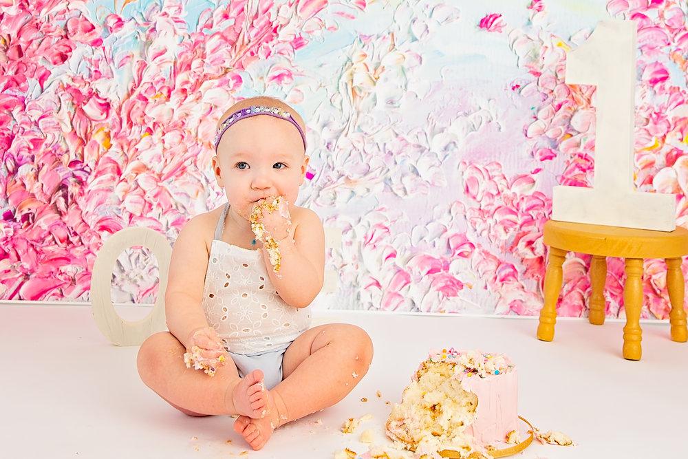 One year old baby girl eating smash cake