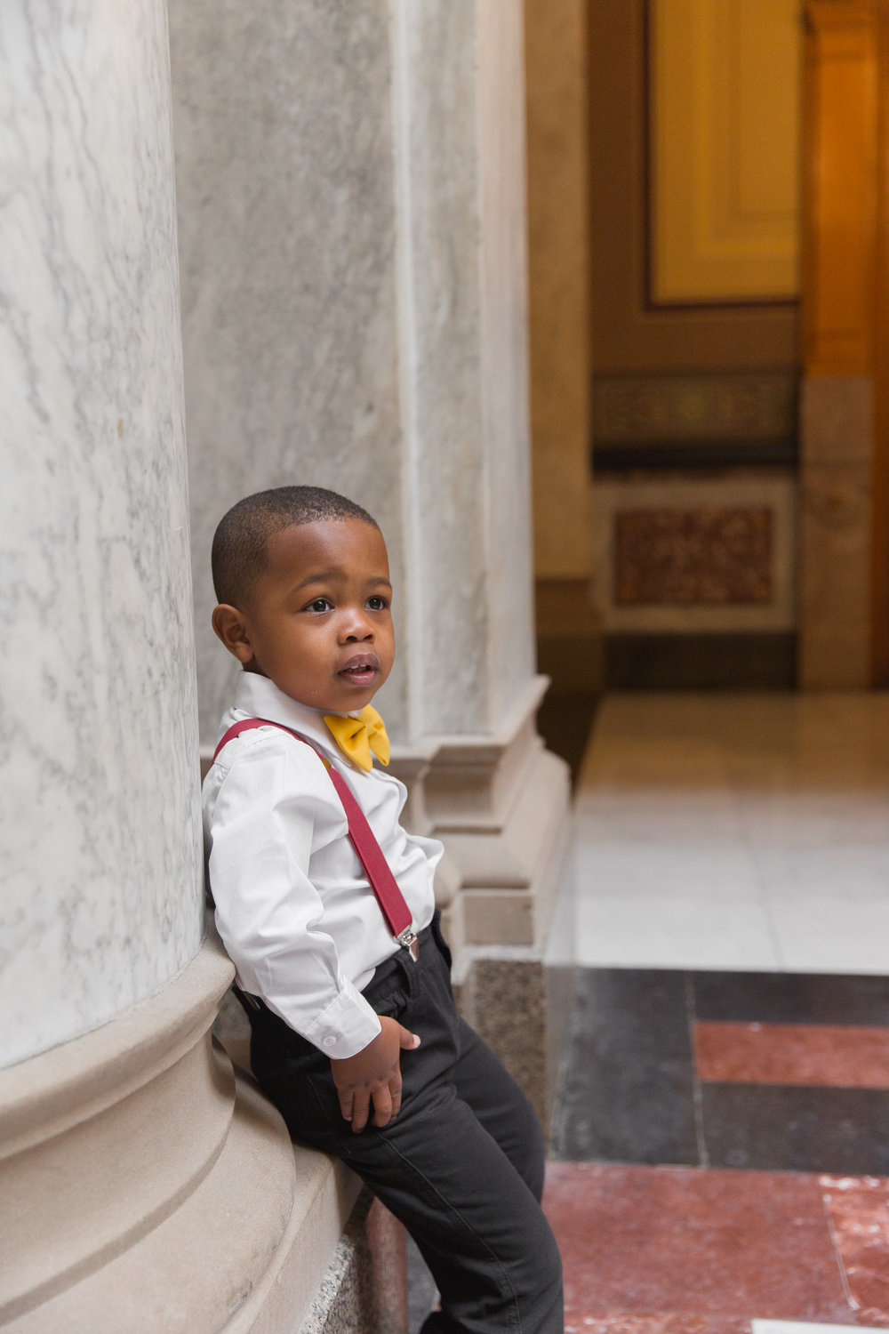 ring bearer in suspenders, leaning up against a wall