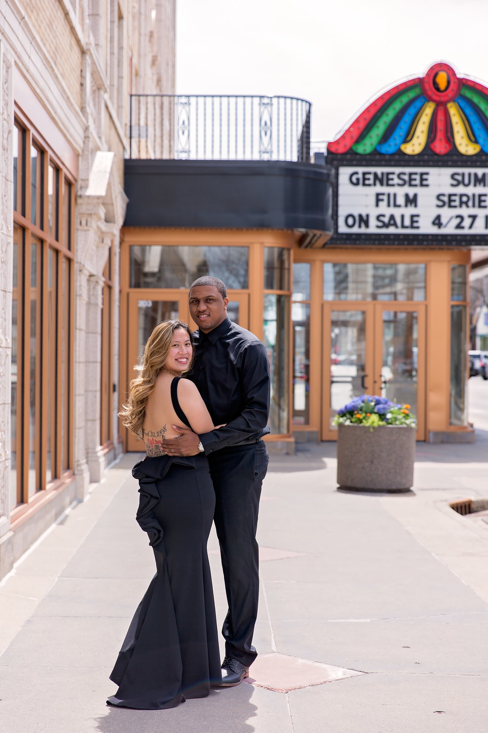 married couple posing on city street