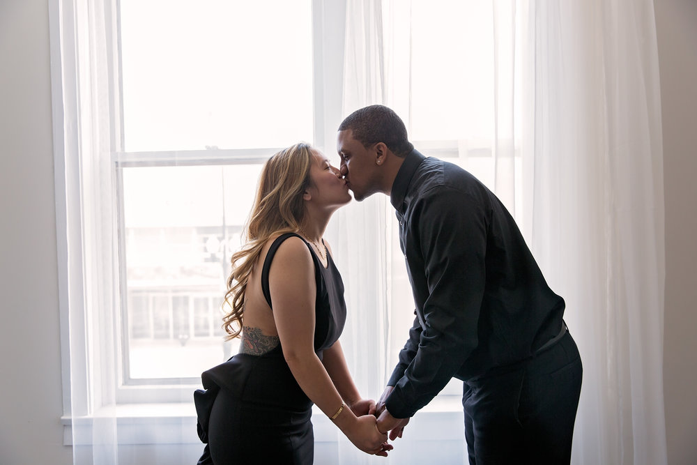 husband and wife kissing in front of windows during couple session