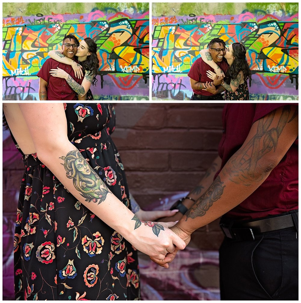 close up of engaged couple holding hands and laughing in front of street art