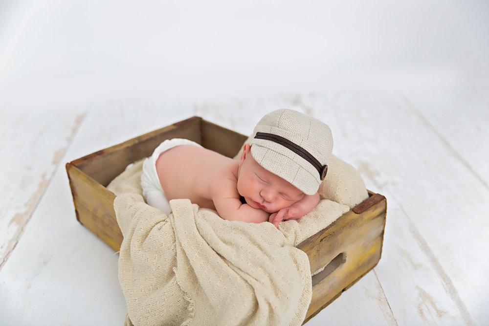 newborn baby posed in prop