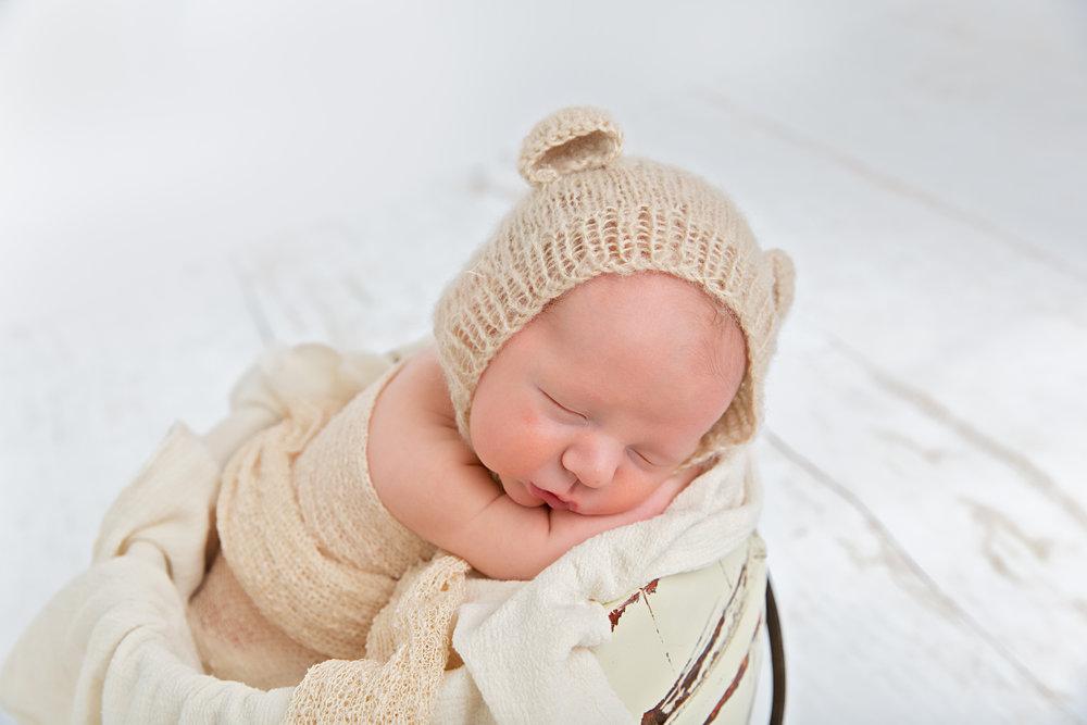 newborn baby sleeping in prop pose