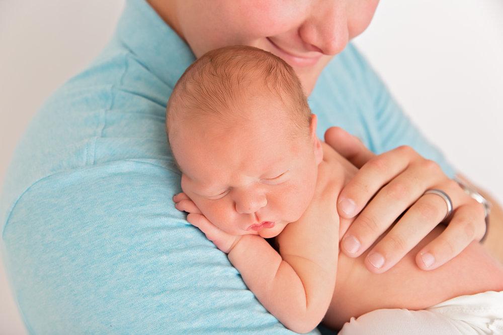 newborn baby sleeping snuggled on daddy