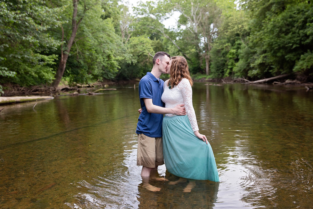 engaged couple kissing while wading in water of creek