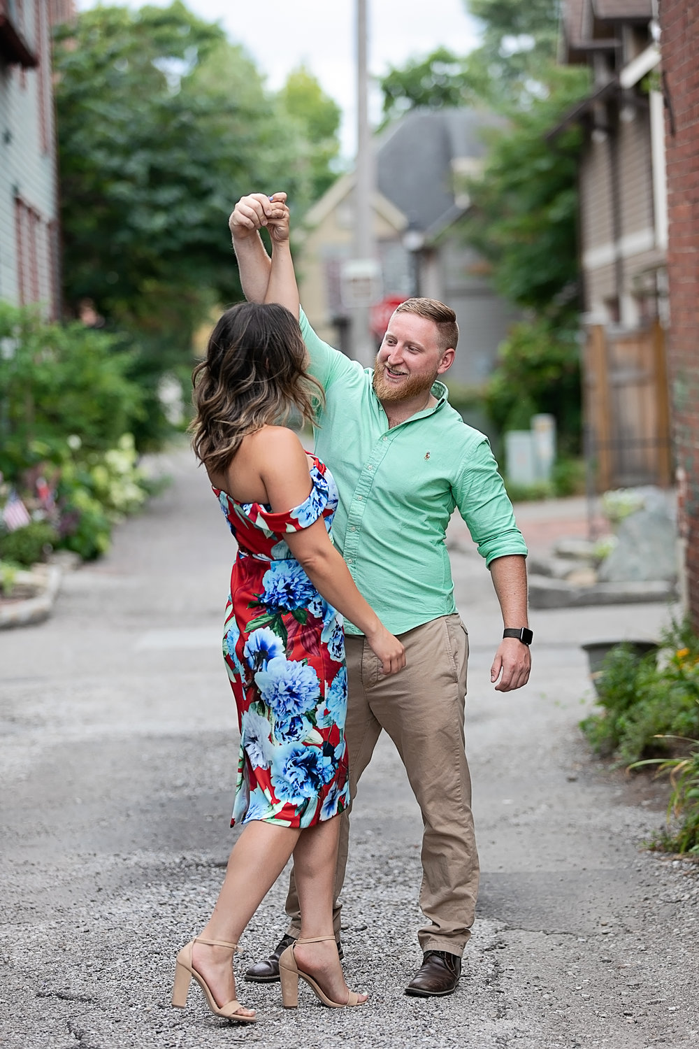 engaged couple dancing on a city street