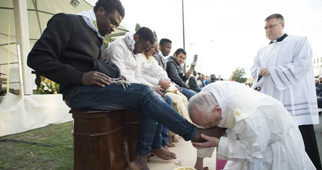 Pope Francis washing the feet of migrants, three of whom were Muslim.