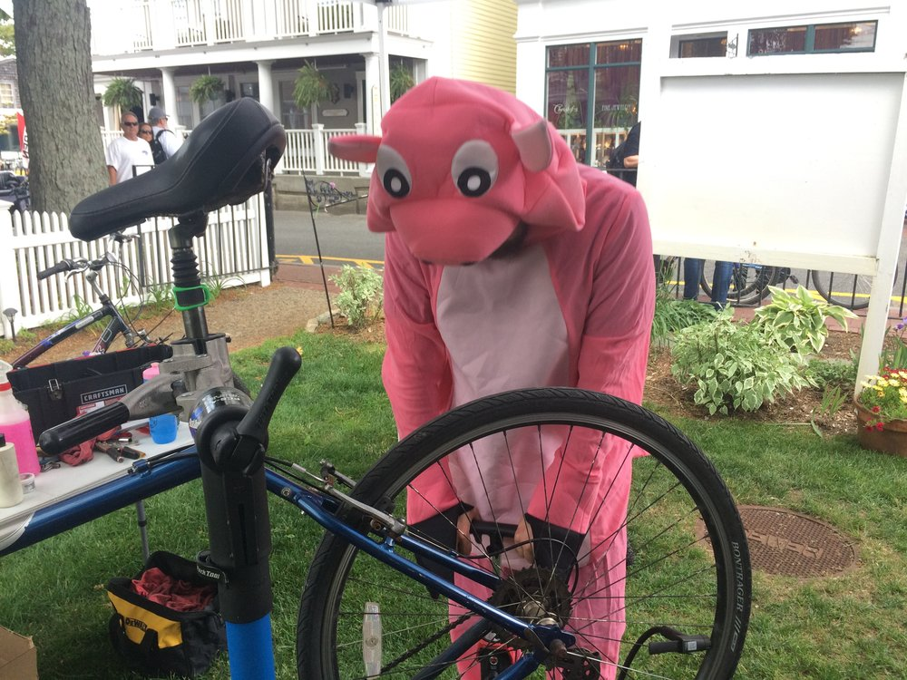 A volunteer mechanic from Ptown Bikes doing a safety check in his pink pig costume.