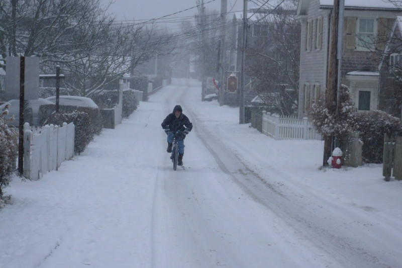 Riding a bike down Provincetown's Commercial Street in the winter snow.