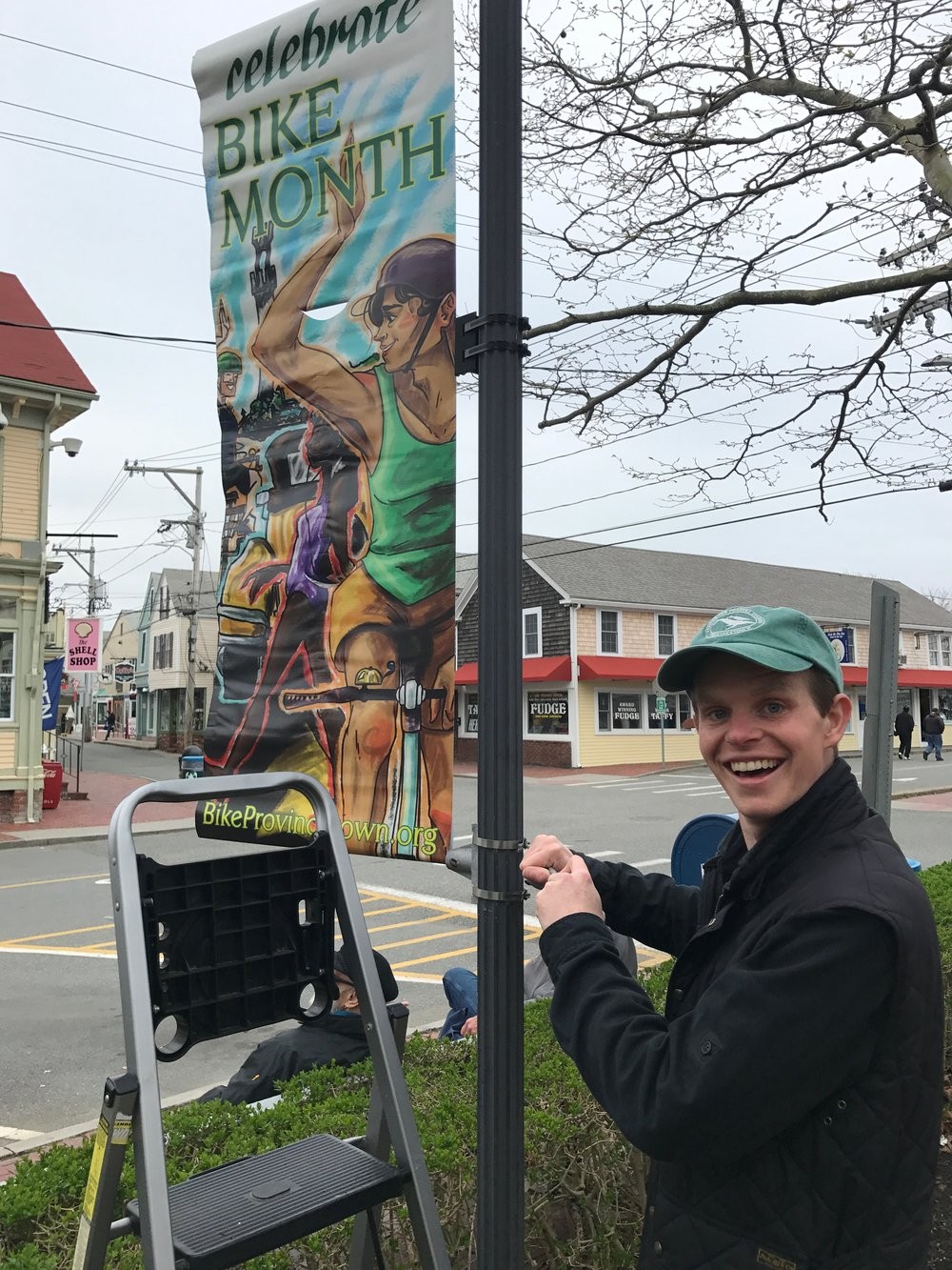 Hanging the Bike Month banners in Portuguese Square on Ryder Street in Provincetown.