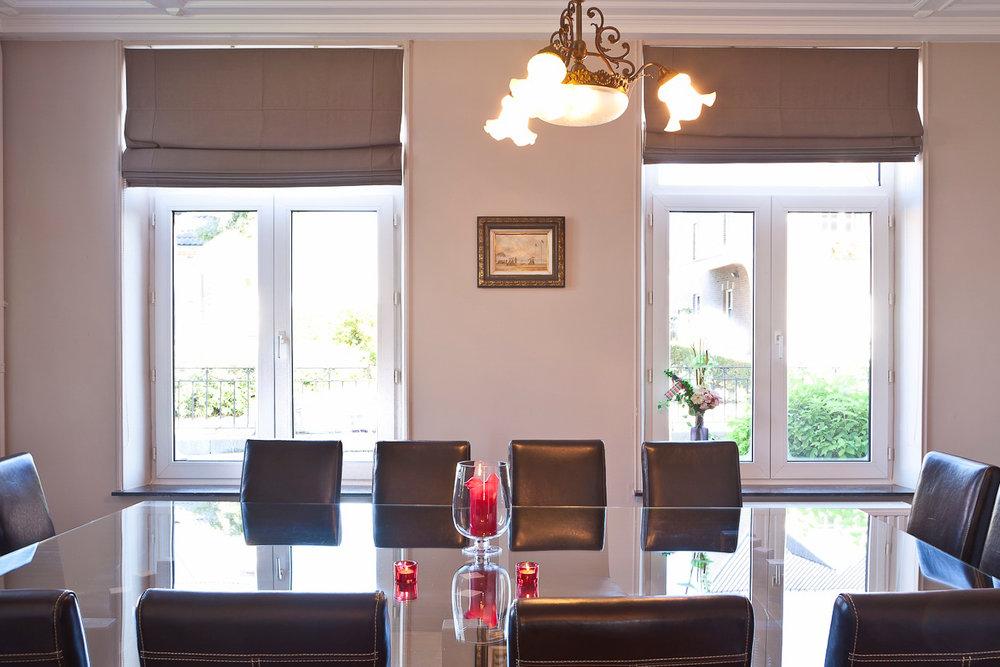 Salle à manger - Une grande table en verre prévue pour 14 personnes et une baie vitrée donnant sur une terrasse, vue sur le jardin.