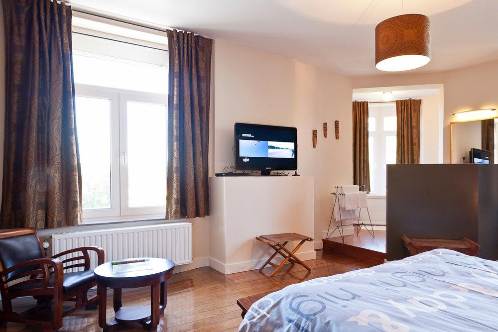 Chambre 1 - Un coin lecture, et une salle de bain avec bain à bulles dans la tour. WC séparé et TV.