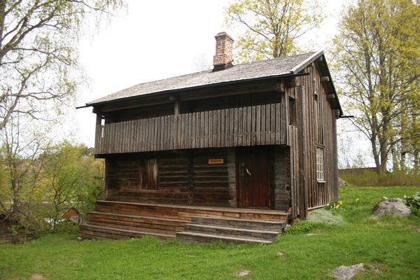 """2. Luhtiaitta..2. Loftsbodan - ....Kaksikerroksinen luhtiaitta, molemmissa kerroksissa kaksi huonetta sekä luhti. Ainutlaatuista on, että yhdessä pohjakerroksen huoneessa on tulisija. Rakennusta on ennen kutsuttu """"Petterin aitaksi"""" koska siinä asui alivuokralaisena viljatorppari Petter Forsblom (1856-1934) Sofia-vaimoineen. Yläkertaa on käytetty asuntona ja vierashuoneena aina 1980-luvulle asti, ja alakerran toista huonetta käytetään näyttelytilana ja pienenä myymälänä...Loftsbod med två våningar med två rum var, samt svale. Ovanlig så till vida att det ena rummet på nedre planet har eldstad. Byggnaden har tidigare kallats för """"Pettersbodan"""" efter spannmålstorparen Petter Forsblom (1856-1934) som bodde som inhysing i byggnaden med sin fru Sofia. Övre våningen har använts som bostad och gästrum ända in på 1980-talet, och ett av rummen på nedre våningen används som utställningslokal....."""
