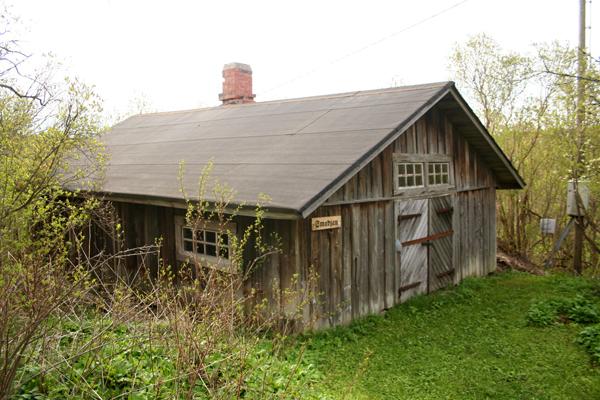 """15. Paja..15. Smedjan - ....Paja oli aiemmin alempana tien varrella ja käytössä noin 1860-1950. Se seisoo siinä, missä """"Vaatturi-Anten"""" talo seisoi 1940-luvulle asti. Vaatturin talo oli kopio Lina Sandströmin talosta, ja siinä asui ja työskenteli ainakin kolme sukupolvea vaattureita. Sepän paja lahjoitettiin vuonna 1968 BUF:ille ja se sisältää täysilukuisen kokoelman sepän työkaluja. Kokoelman lahjoitti Postimäelle vuonna 1977 Sandströmin sepän lapsenlapsi Knut, myös seppä ammatiltaan...I användning nere vid vägen ca 1860-1950. Står där """"Skräddar-Antes"""" hus stod fram till 1940-talet. Skräddarns hus var en exakt kopia av Lina Sandströms stuga där åtminstone tre generationer skräddare bodde och arbetade. Smedjan donerades år 1968 till BUF och innehåller en komplett uppsättning smidesverktyg som donerades 1977 av smeden Sandströms son Knut, också smed till yrket....."""