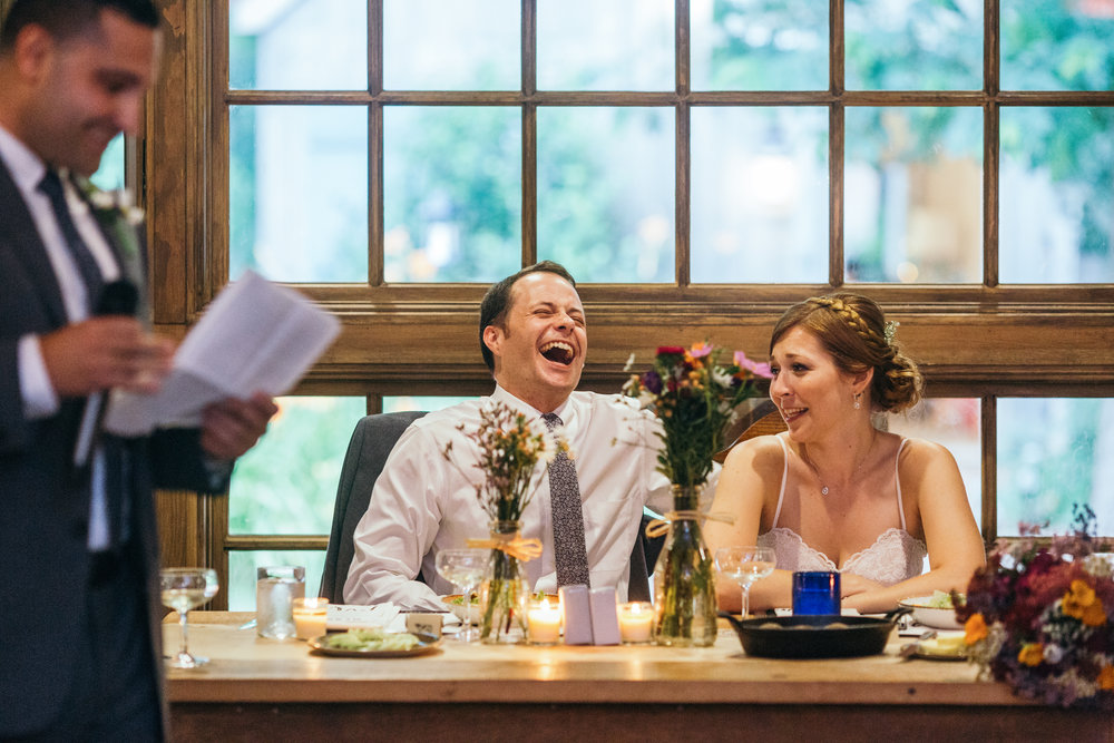 Bride and groom during their dinner reception at their rustic Waterloo Village wedding listening to toasts