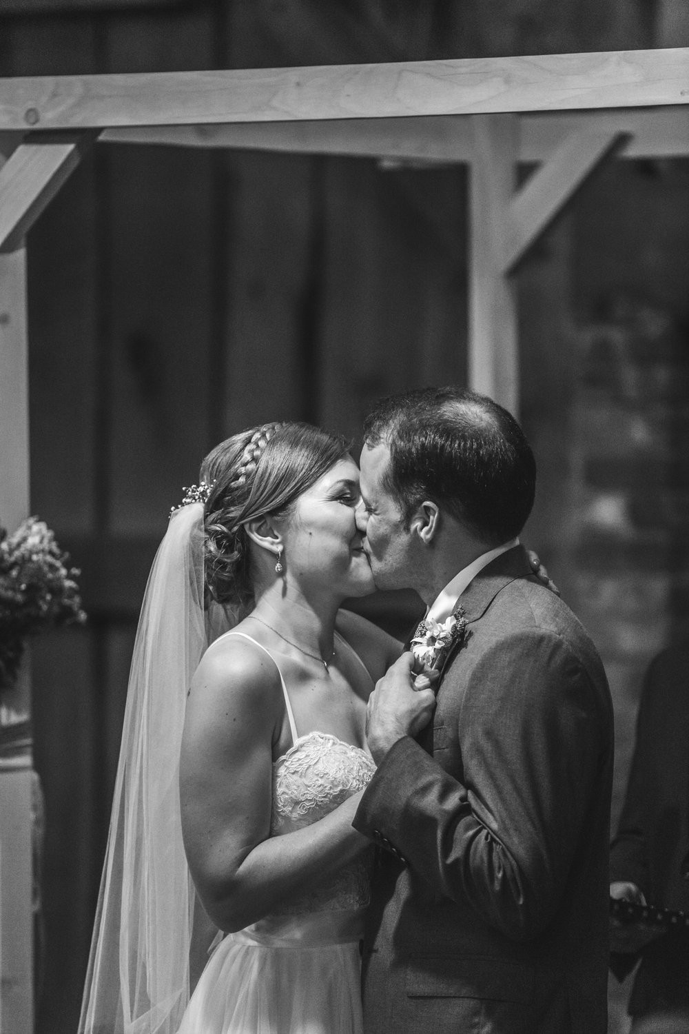 Black and White photo of Bride and Groom kissing after their wedding ceremony in their rustic barn wedding at Waterloo Village