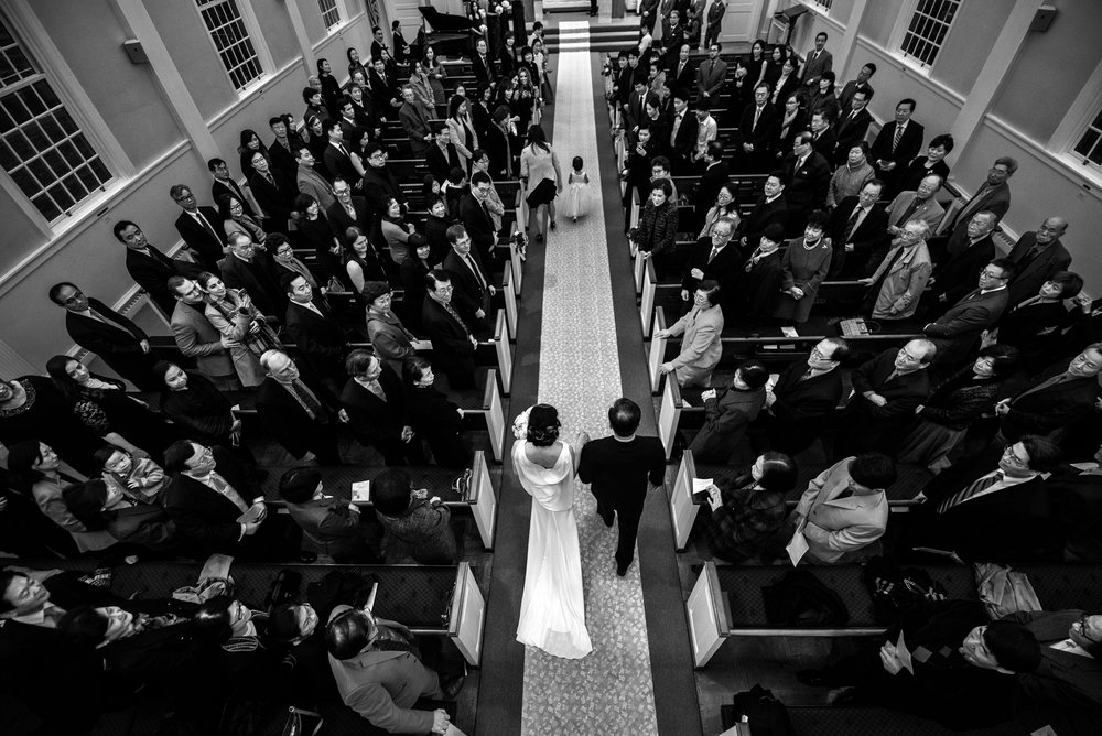Aerial black and white shot of sustainable wedding celebration of bride escorted by father walking down the aisle of a church ceremony