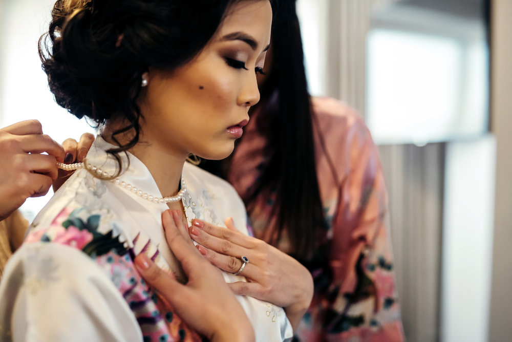 Portait of beautiful asian bride with hair and makeup done getting a pearl necklace put on her while wearing floral vintage inspired robe at the Westin hotel Jersey City