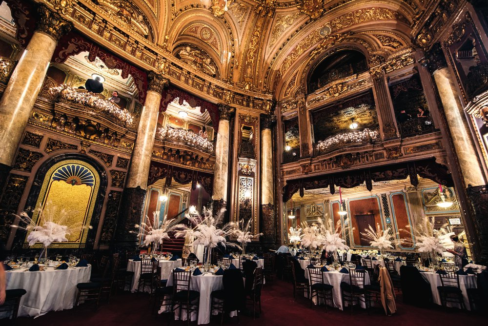 Beautifully 20's Inspired decorated reception hall at historic Loew's Theater in Jersey City with feather center pieces and black and gold theme