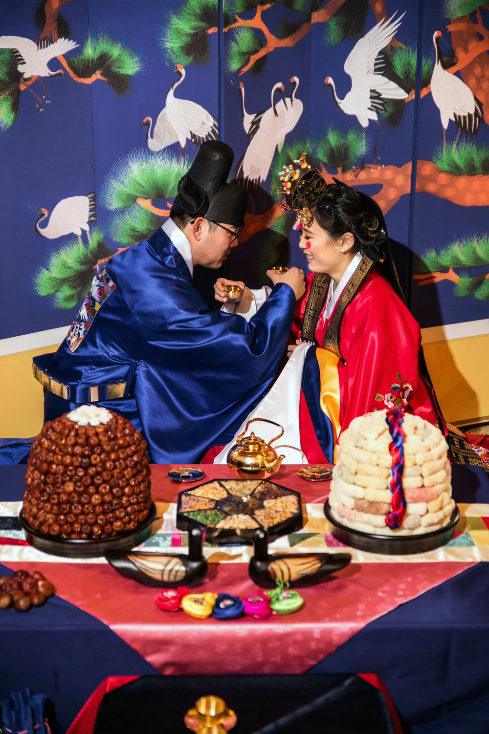 Traditional Korean tea ceremony during sustainable wedding reception of bride and groom celebrating a momentus occasion while wearing native garb