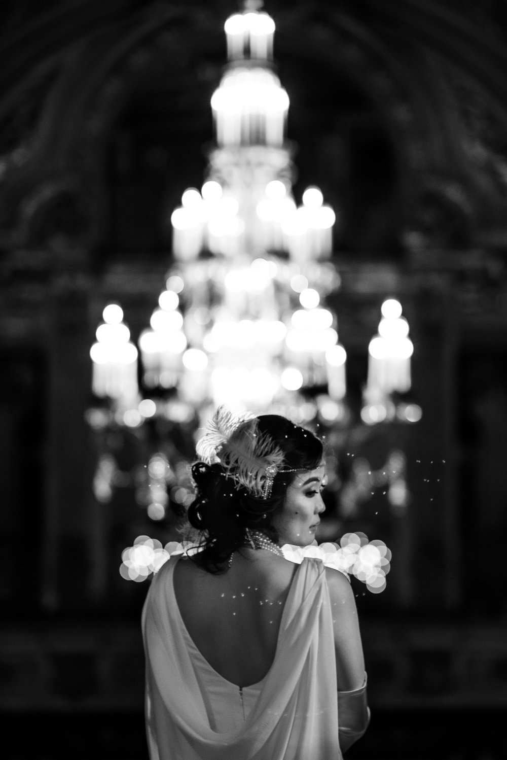 Stunning black and white portrait of bride's white backless gown and 20s inspired feather head piece and pearl necklace
